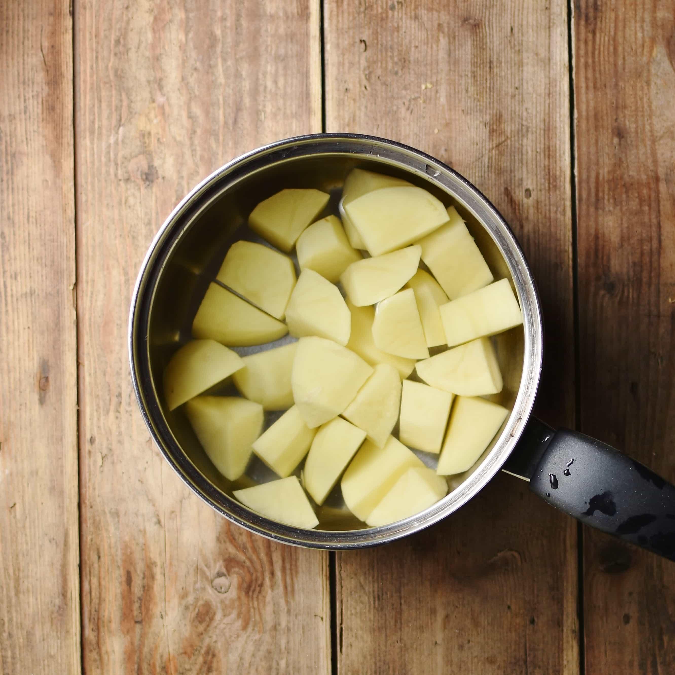 Cubed potatoes in water inside saucepan.