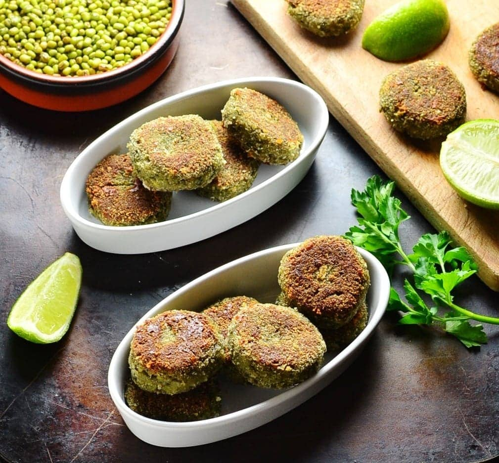 Side view of mushroom cakes in white oval dishes with lime, beans in brown dish and cutting board on oven tray.