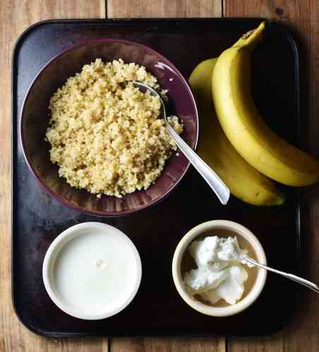 Cooked quinoa in purple bowl with spoon, 2 bananas, yogurt in small dish with spoon and milk in another dish.