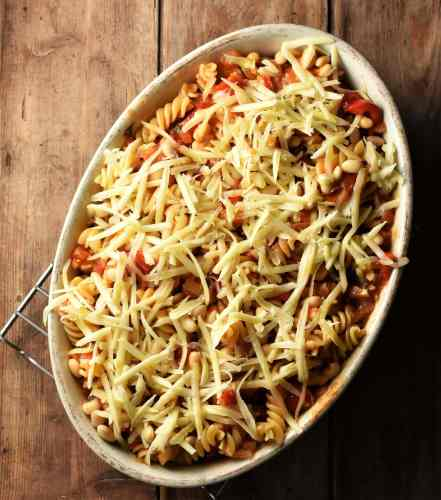 Fusilli pasta with tomato sauce and grated cheese in white oval casserole dish.
