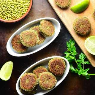 Top down view of mung bean mushroom patties in white oval dishes with lime, beans in brown dish and cutting board on oven tray.