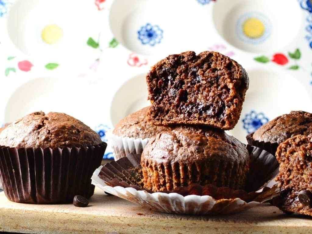 Side view of chocolate quinoa muffins on top of cutting board with muffin pan in background