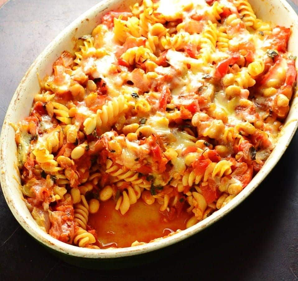 Top down view of bean pasta bake in oval casserole dish on oven tray
