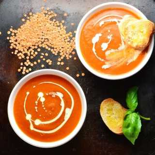 Top down view of tomato and lentil soup in 2 white bowls with toasted bread, lentils and basil leaves on oven tray.