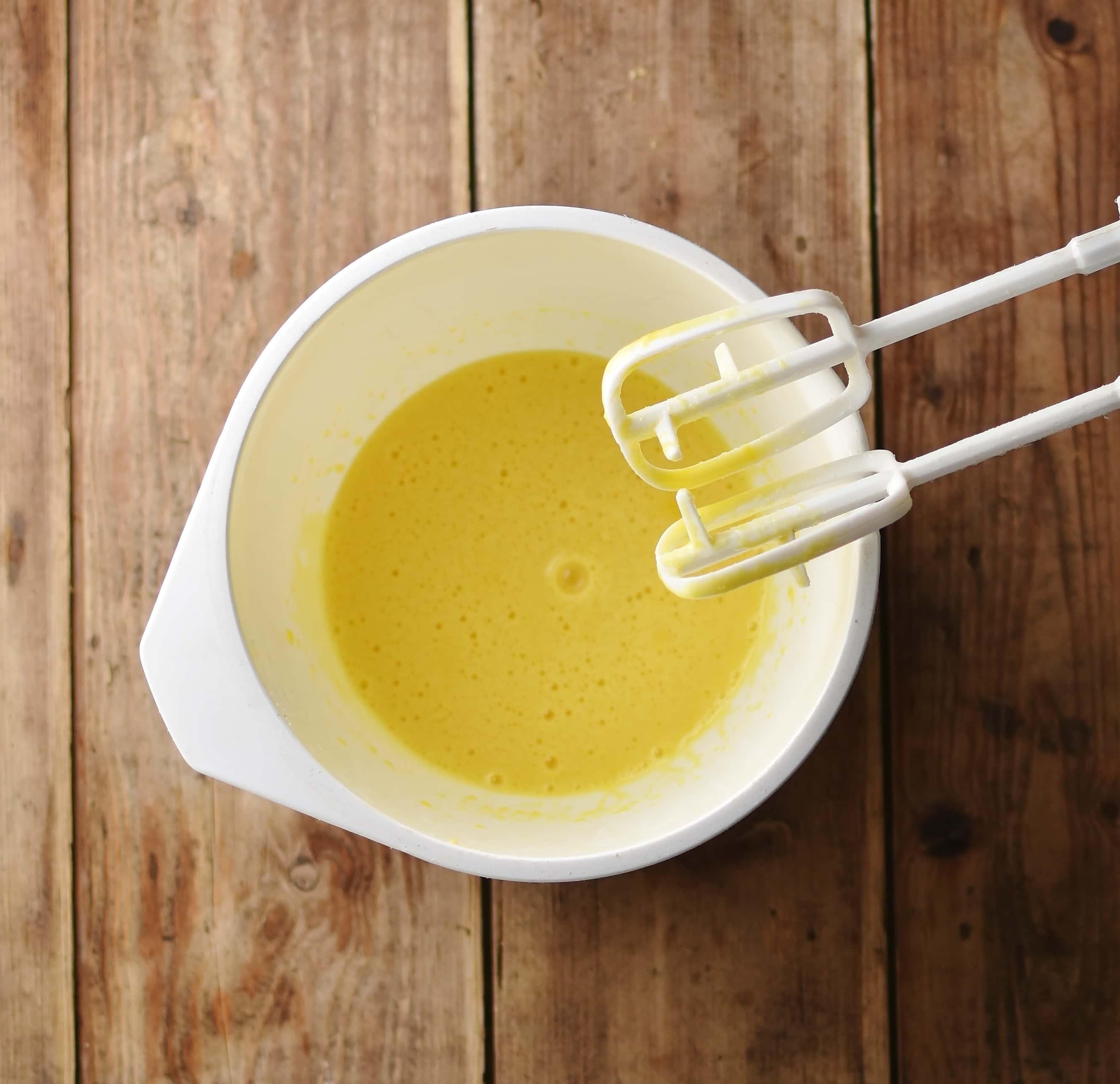 Beaten eggs and oil inside white bowl.