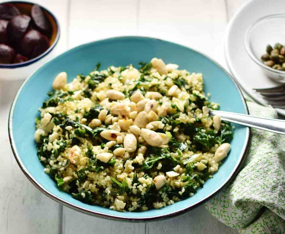 Bulgur wheat with kale and almonds in blue bowl with spoon, green cloth in bottom right corner and small dish with baby beets in top left.
