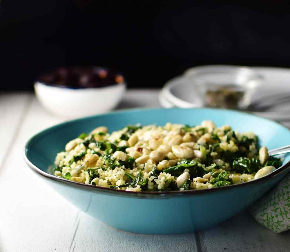 Side view of bulgur wheat with kale in blue bowl, with white plated and small white dish in background.