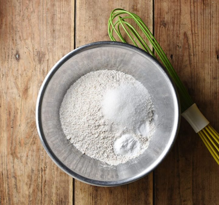 Flour mixture in metal bowl with green whisk to the right.