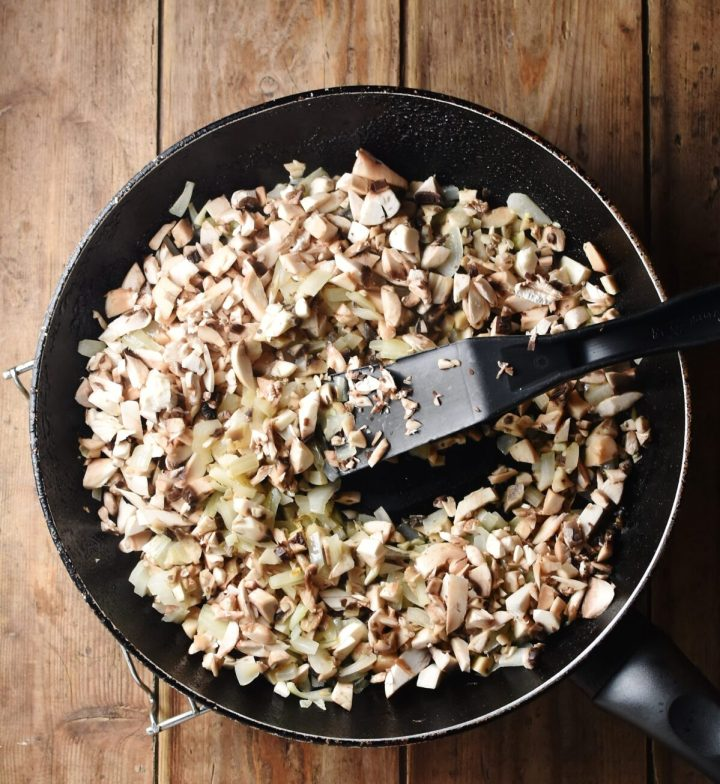 Chopped mushrooms and onion in skillet with black spatula.