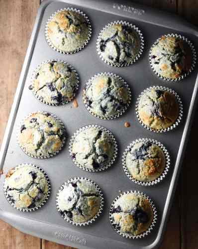 Baked blueberry muffins inside 12-hole muffin pan.