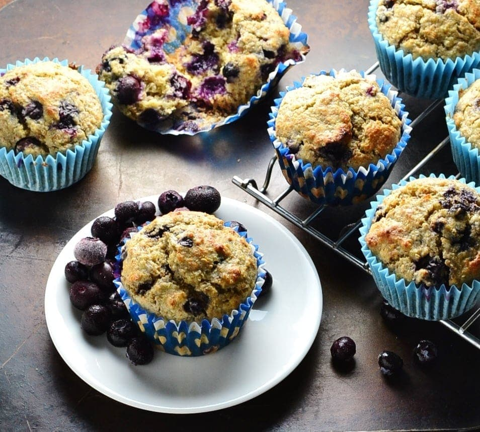 Blueberry muffins on top of dark surface with small white plate and cooling rack.