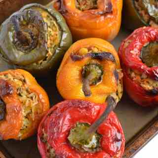 Yellow, red and green stuffed peppers in oven tray.