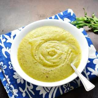 Top down view of cream of zucchini soup in white bowl with spoon on blue cloth.