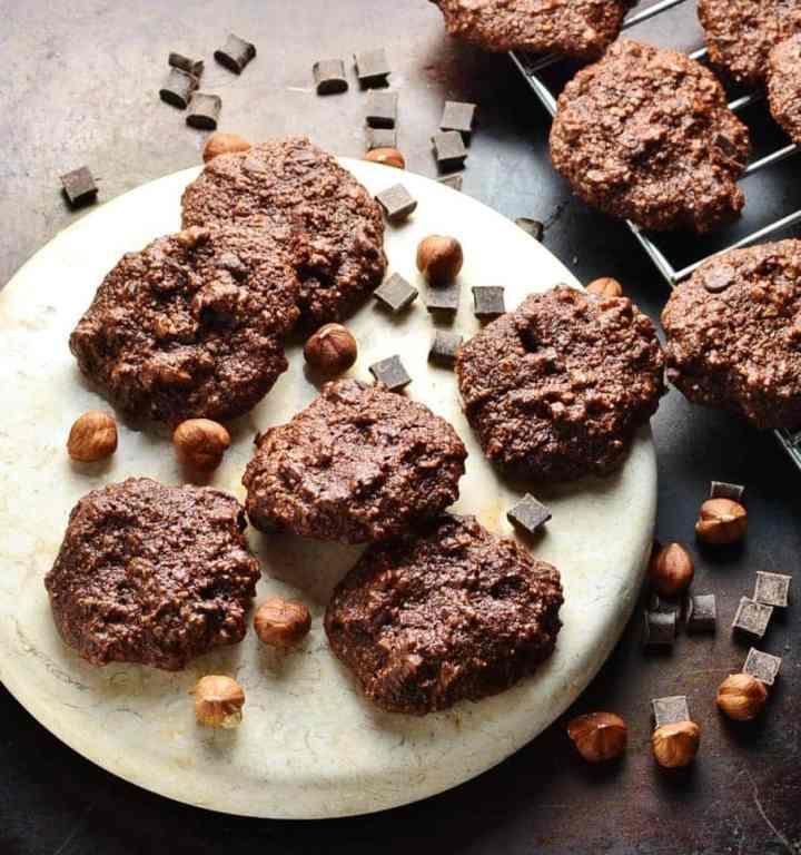 Chocolate hazelnut cookies on white round plate with chocolate chunks and hazelnuts.
