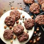 Top down view of chocolate cookies on white plate with hazelnuts and chocolate chunks on oven tray.