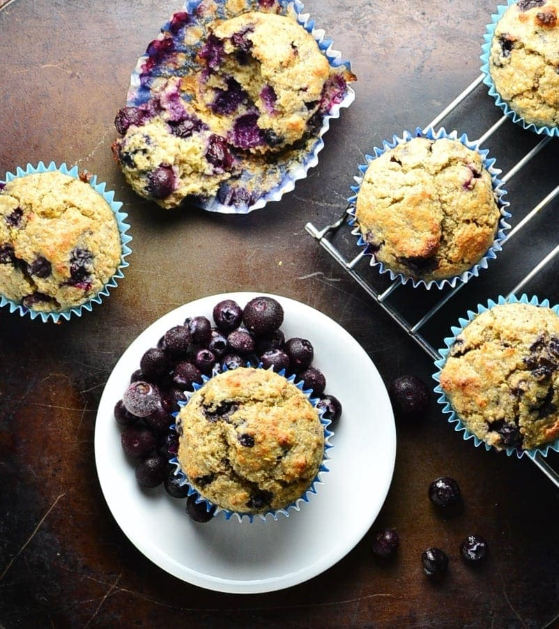 Top down view of blueberry breakfast muffins on oven tray with small white plate and cooling rack.
