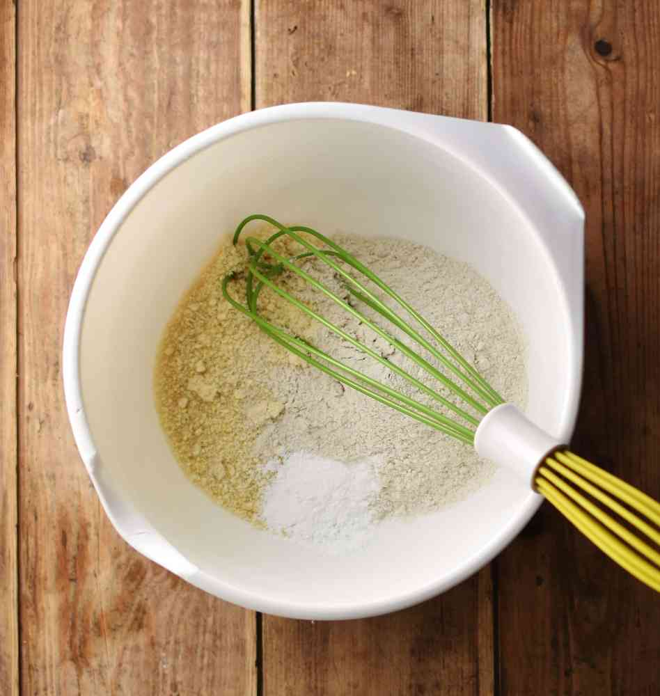Dry banana bread ingredients with green whisk inside white bowl.