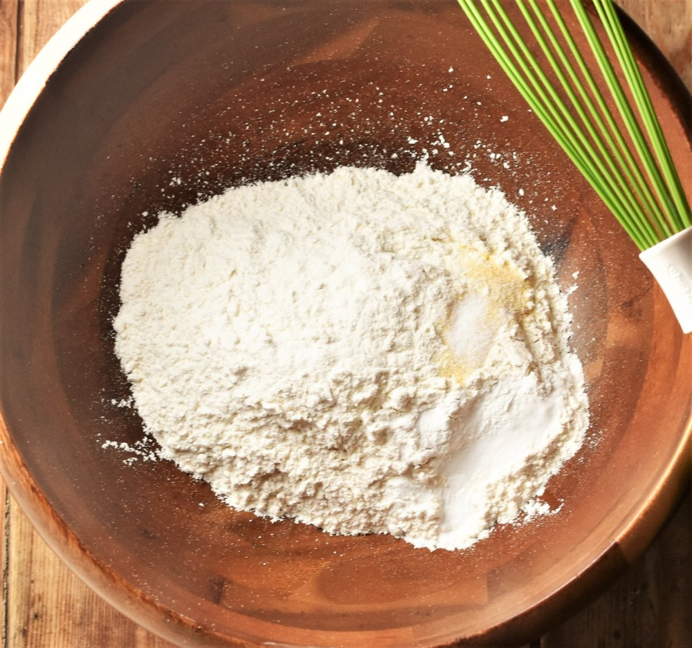 Dry ingredients in wooden bowl with green whisk to the right.