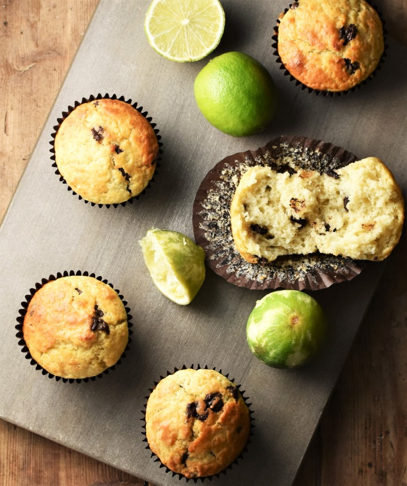 Lime chocolate chip muffins in brown cases and limes on top of grey wooden board.