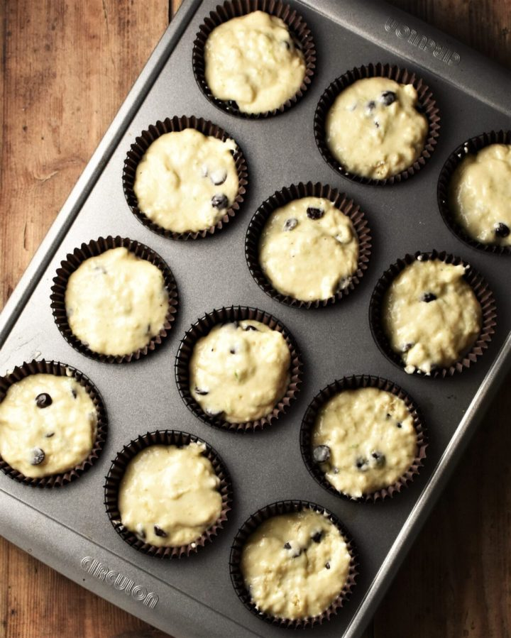 Muffin batter in 12 brown cases in muffin pan.