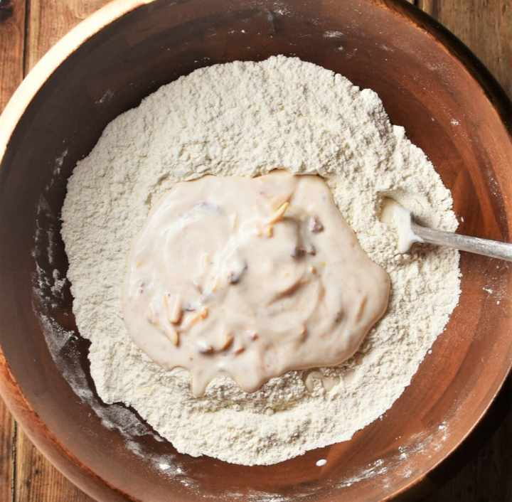 Flour and buttermilk in wooden bowl with fork.