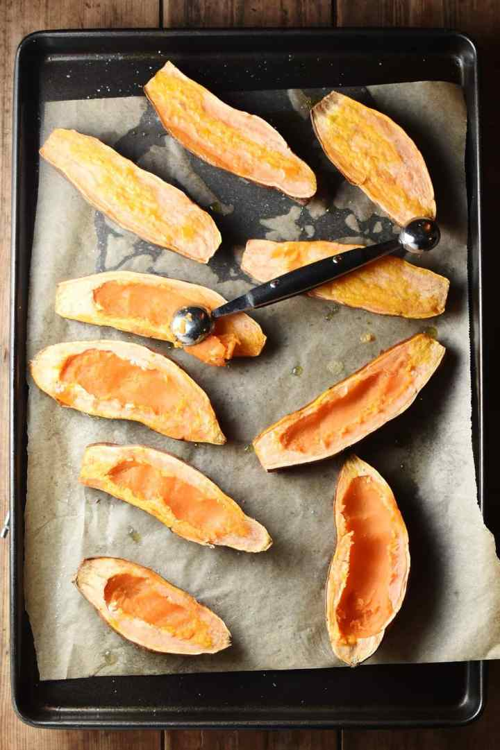 Sweet potato halves with melon baller on top of baking tray lined with paper.