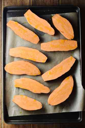 Sweet potato halves on top of tray lined with baking paper.