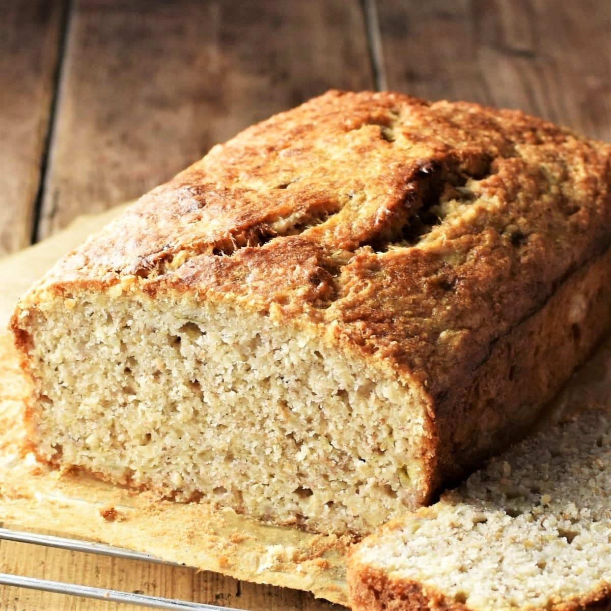 Close-up side view of banana bread with quinoa on top of parchment.