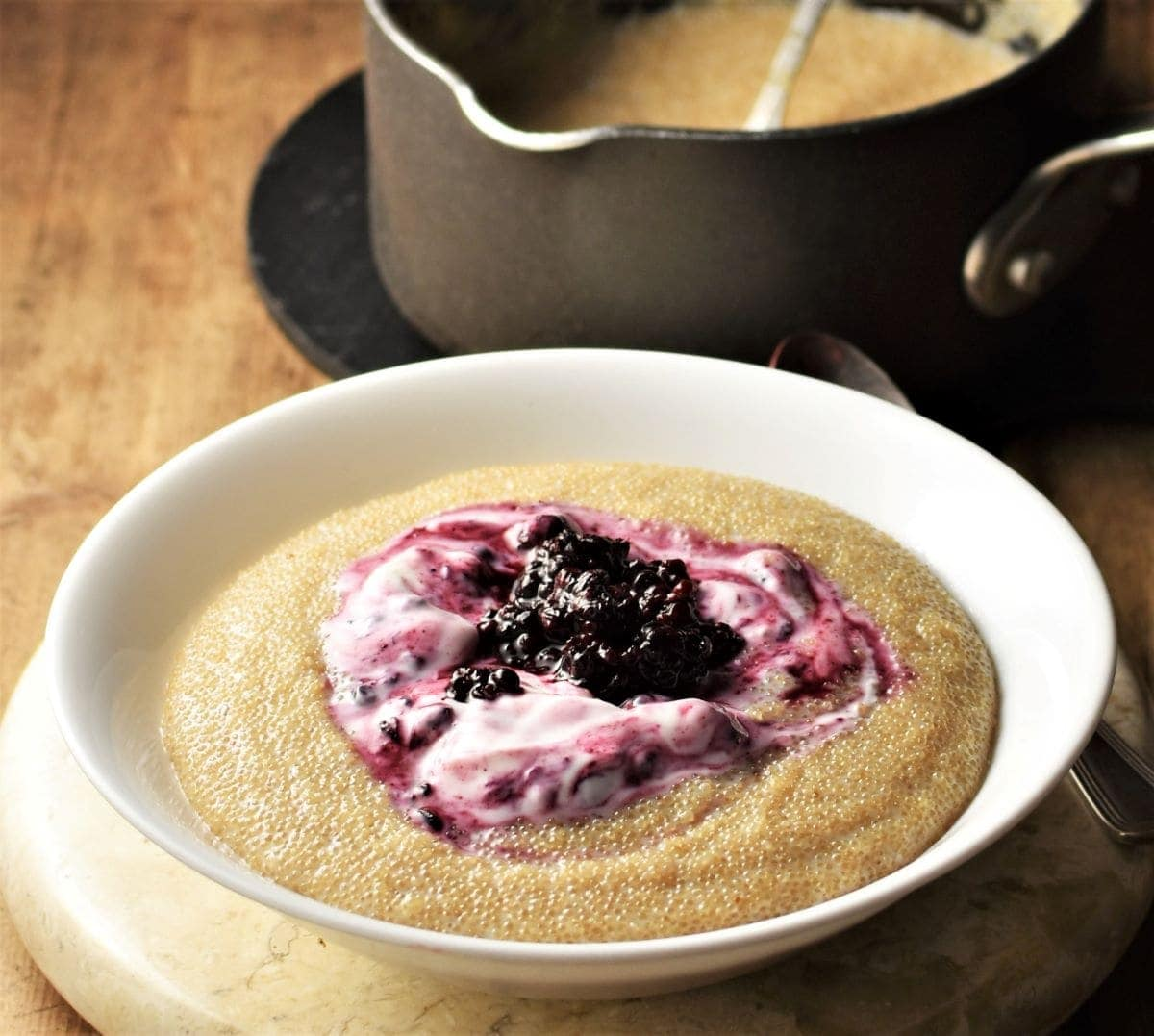 Side view of amaranth porridge with yogurt and fruit in white bowl.