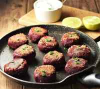 Side view of beetroot patties on top of pan, with yogurt and lemon halves in background.