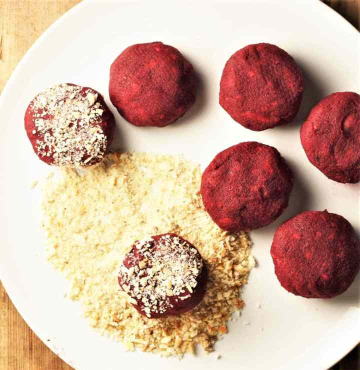 Beet patties with breadcrumbs on top of plate.