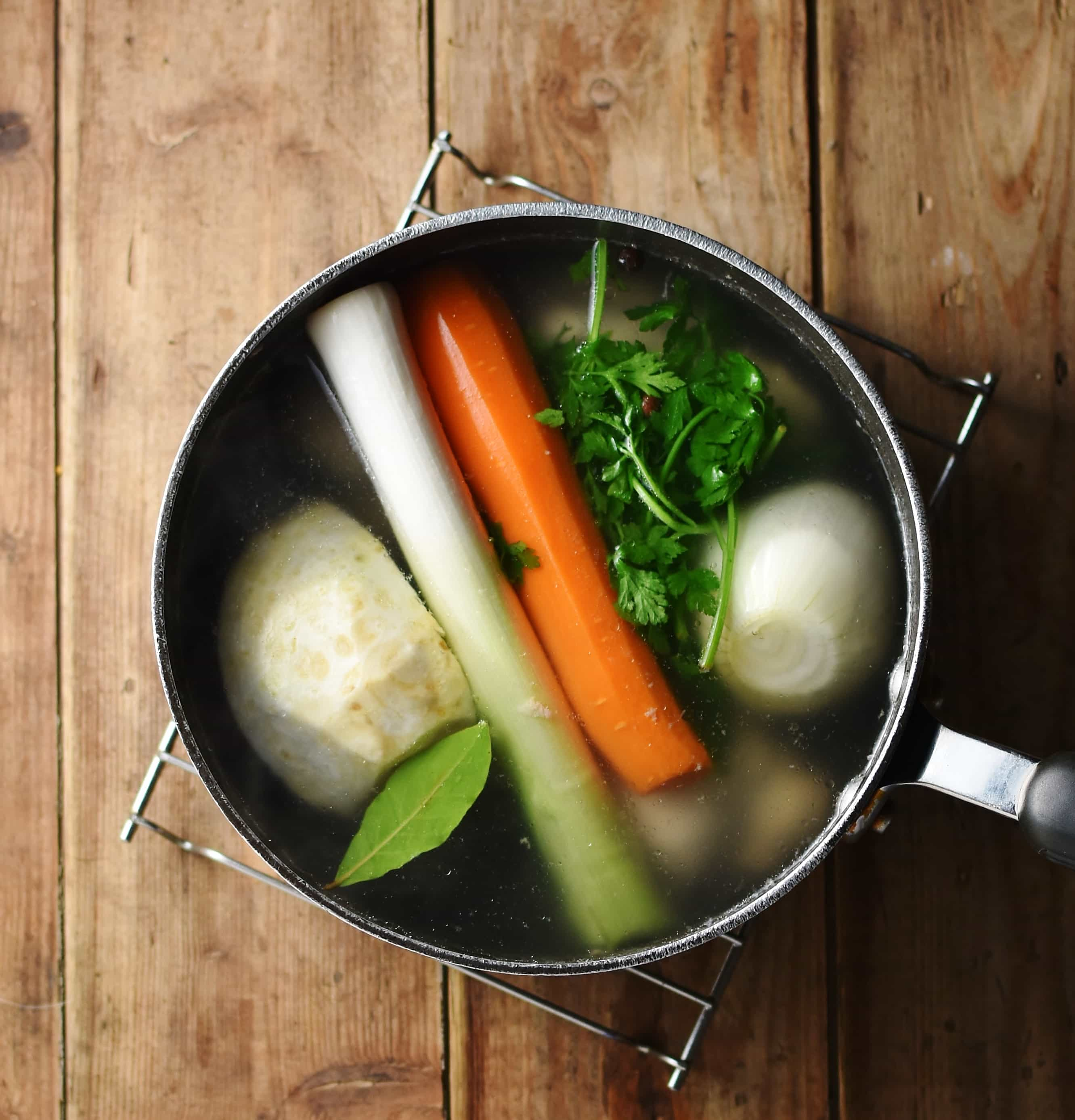 Whole, peeled carrot, onion, leek and celeriac with bay leaf and parsley in large pot with water.