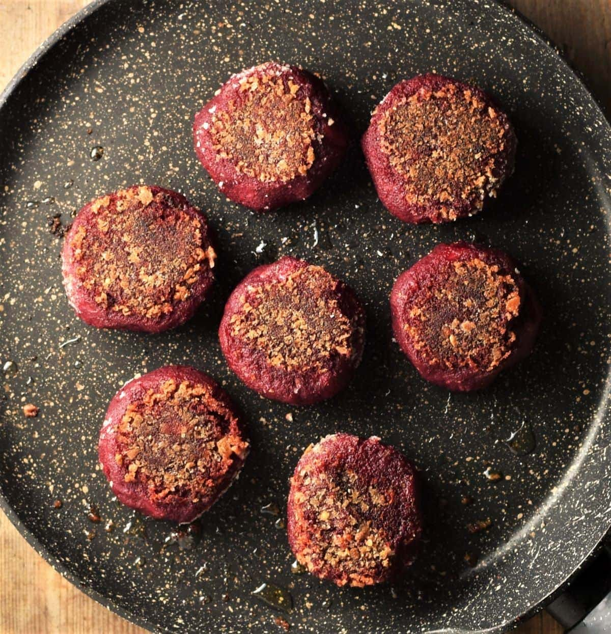 Fried beet cakes on top of large pan.