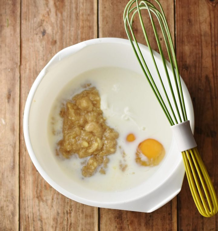 Eggs, milk and mashed banana in white bowl with green whisk.