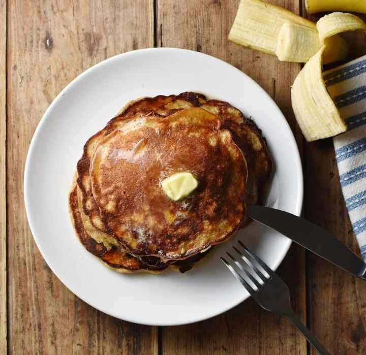 Top down view of pancakes with knob of butter on white plate with fork and knife and cut banana in background.