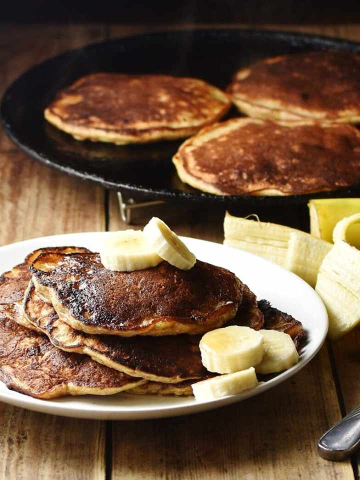 Banana pancakes with banana slices on white plate, with peeled banana, pancakes in pan and utensils on top of blue stripy cloth in background.