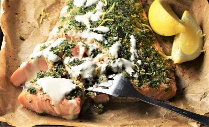 Close-up partial view of herb crusted salmon with creamy sauce, fork and lemon wedges.