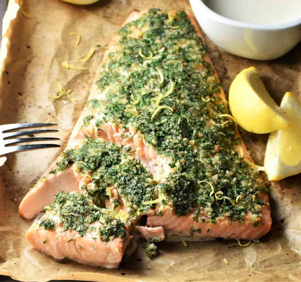Close-up with of herb salmon with lemon wedges.