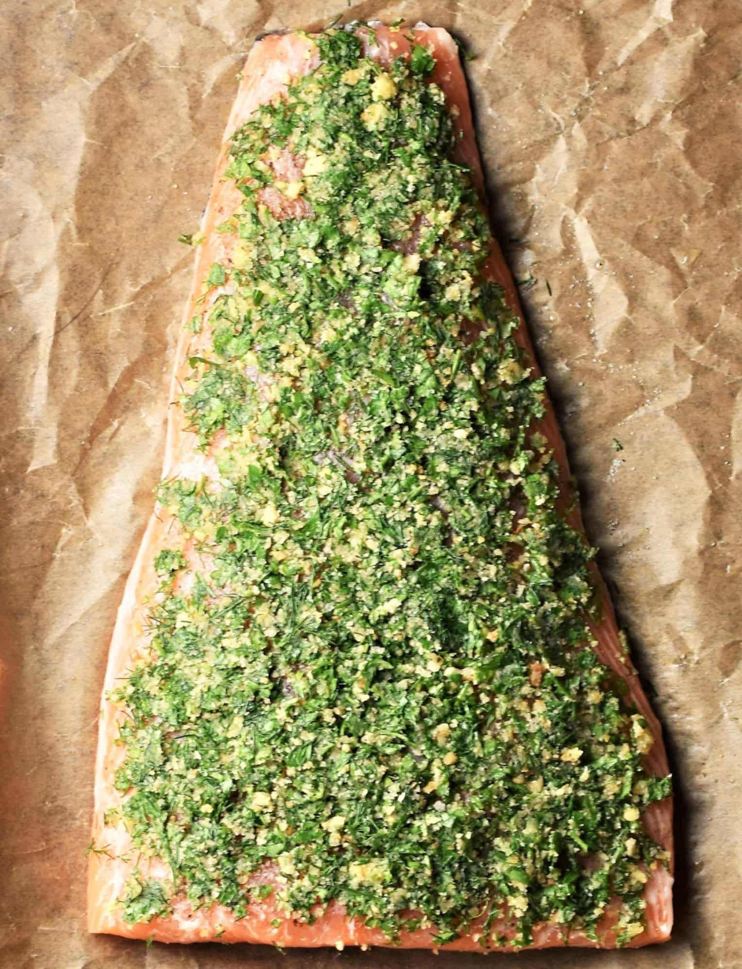 Salmon fillet topped with herb mixture on top of parchment.