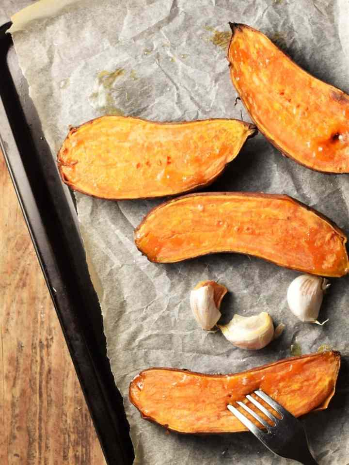Top down view of halved roasted sweet potatoes and garlic cloves on tray lined with parchment paper.
