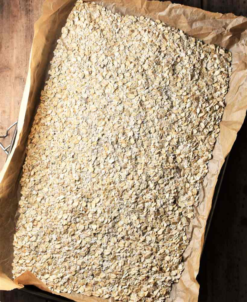 Oats spread over a baking sheet lined with parchment.