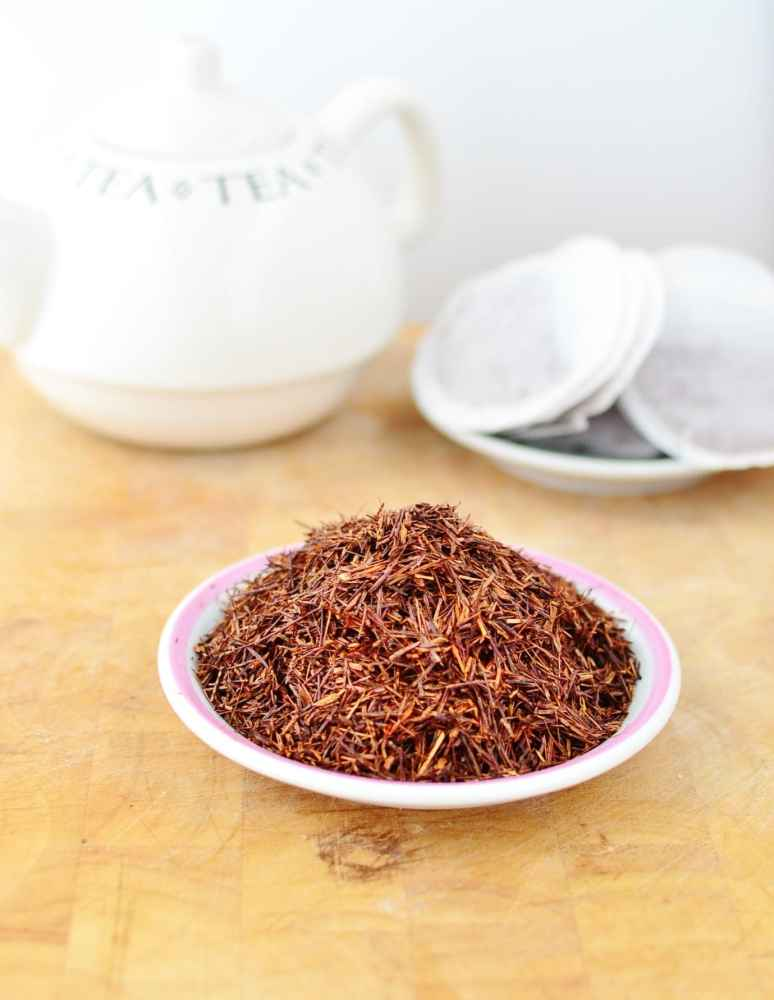 Dried rooibos leaves on top of white plate, with tea bags and white tea kettle in background.