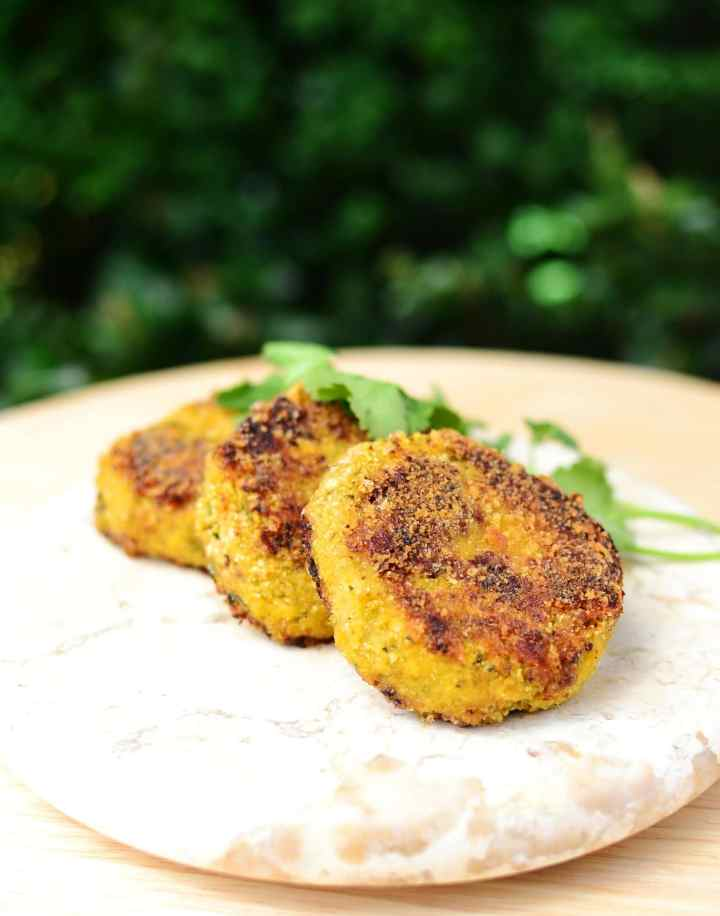 Cauliflower rice patties with cheese on marble plate with bushes in background.