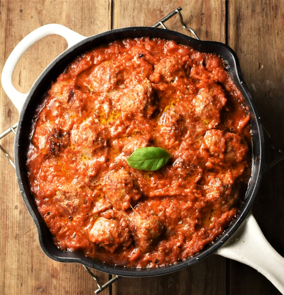 Meatballs in tomato sauce in pan with white handle.