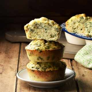 3 quinoa egg muffins stacked on top of small plate, with muffins in background.