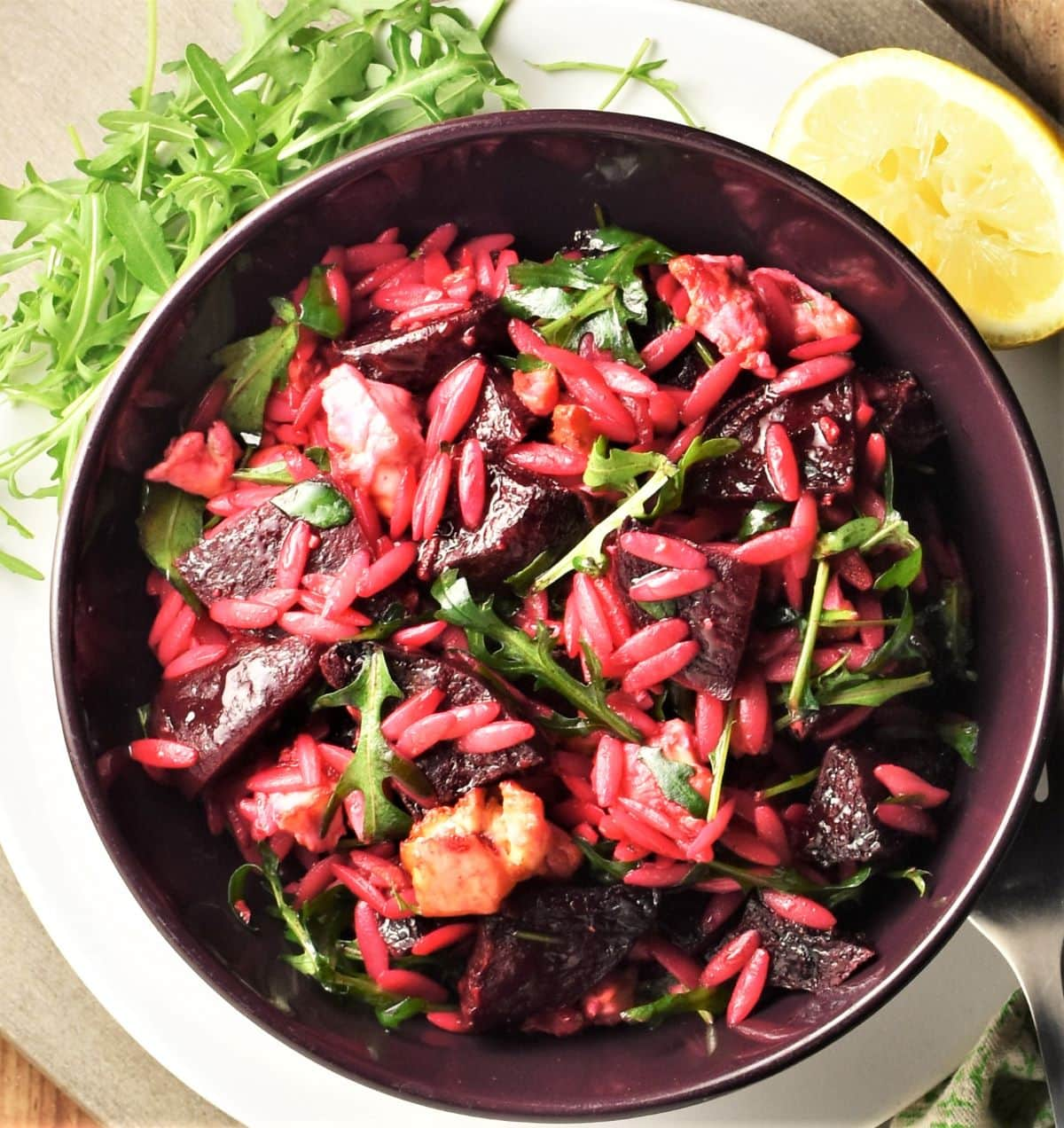 Beet feta salad with pasta in purple bowl.
