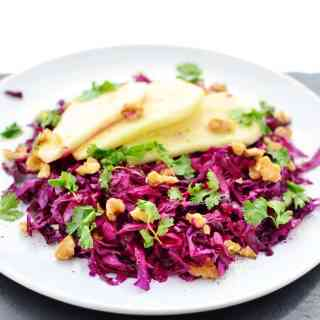 Pickled red cabbage slaw with walnuts, cilantro and pear slices on top of white plate.