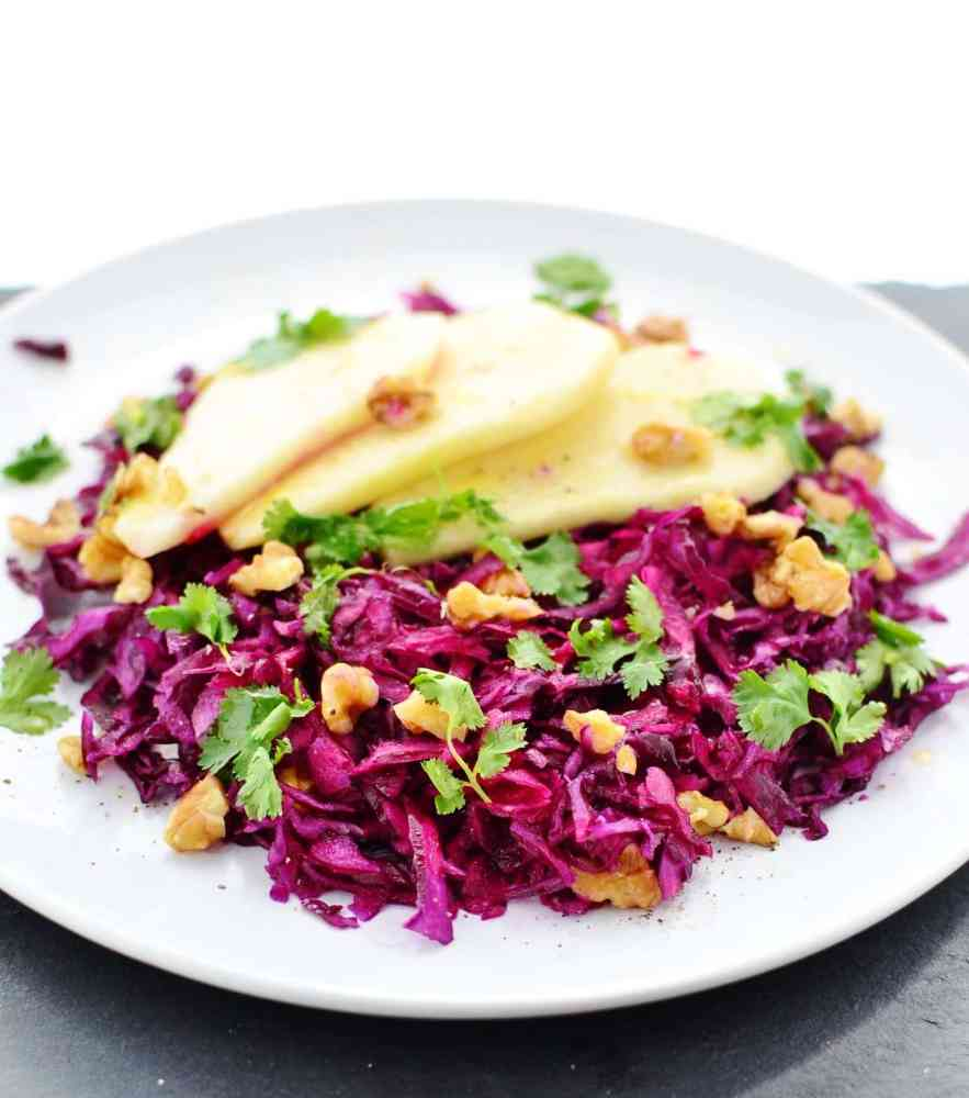 Red cabbage salad with pear on white plate on slate surface.