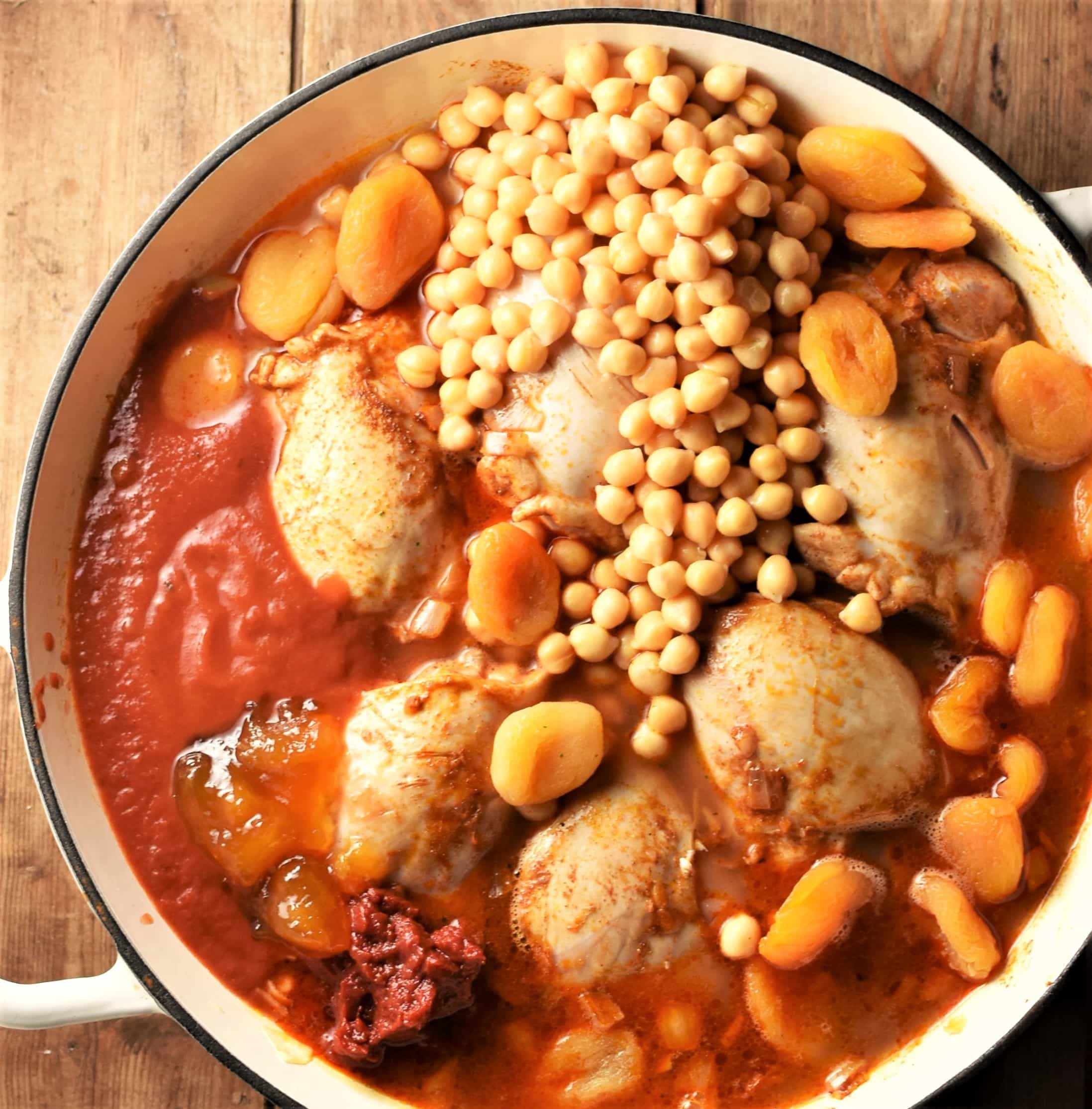 Top down view of chicken, chickpeas, dried apricots in tomato sauce in large shallow dish.
