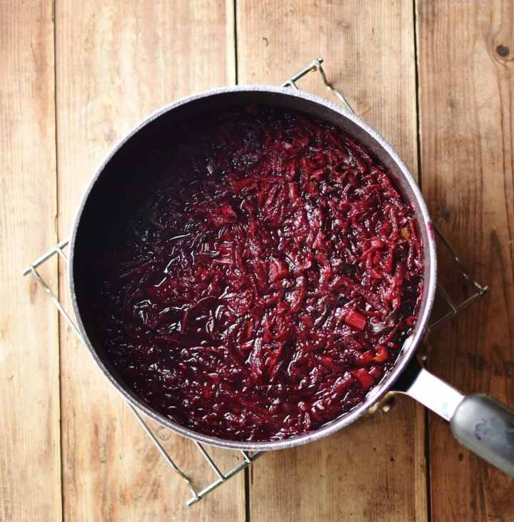 Grated beets with water inside pot on top of cooling rack.